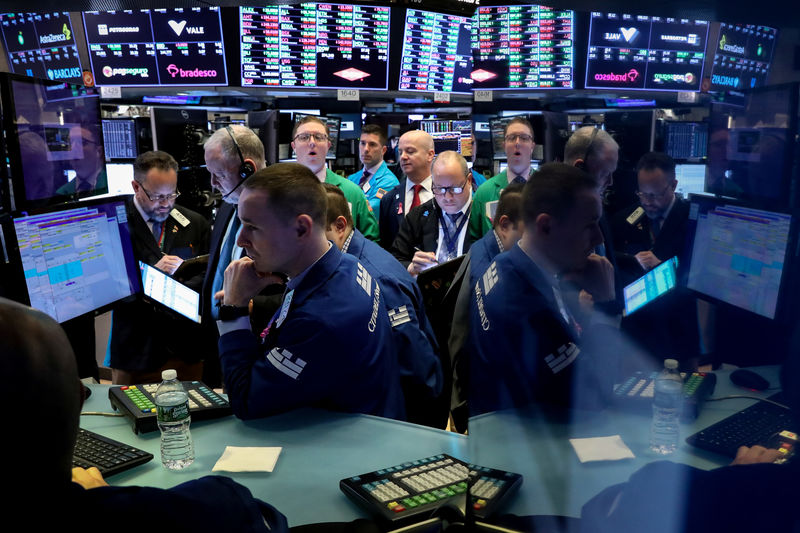 FILE PHOTO: Traders work on the floor at the New York Stock Exchange (NYSE) in New York, U.S., April 4, 2019. REUTERS/Brendan McDermid/File Photo