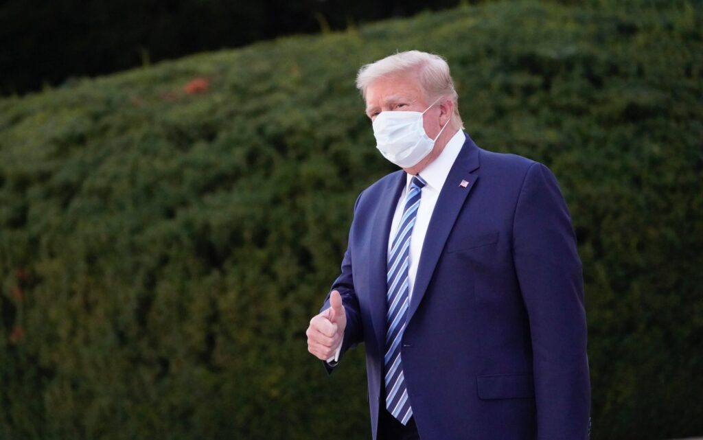 epa08723037 US President Donald J. Trump, wearing a mask, gestures after leaving Walter Reed National Military Medical Center, in Bethesda, Maryland, USA, 05 October 2020, to board Marine One for a return trip to the White House after receiving treatment for a COVID-19 infection.  EPA/Chris Kleponis / POOL