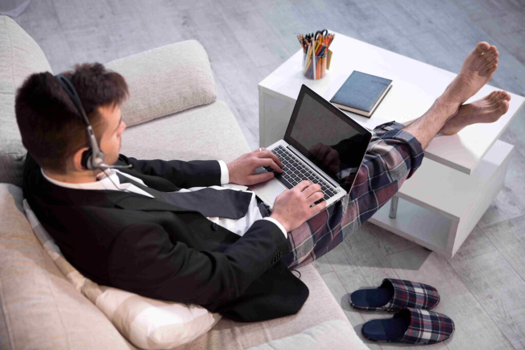 Man typing on laptop working on freelance at home. Up view on a man in casual trousers and jacket keyboarding on computer.