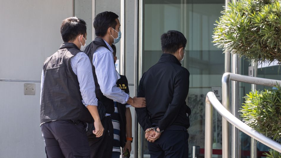 epa09278510 Apple Daily editor-in-chief Ryan Law (R) is escorted by police to the office of Next Media, publisher of Apple Daily, in Hong Kong, China, 17 June 2021. Hong Kong's national security police arrested Law and four other directors of the Apple Daily newspaper on suspicion of conspiracy to collude with foreign forces, under China-imposed legislation.  EPA/JEROME FAVRE