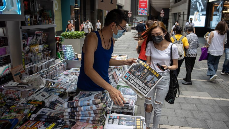 epa09281729 A woman buys a copy of Apple Daily newspaper at a news stand in Hong Kong, China, 18 June 2021. The pro-democracy newspaper made print-run of 500,000 for 18 June 2021, a day after Hong Kong?s national security police arrested five directors at the newspaper on suspicion of conspiracy to collude with foreign forces under the China-imposed legislation. EPA/JEROME FAVRE